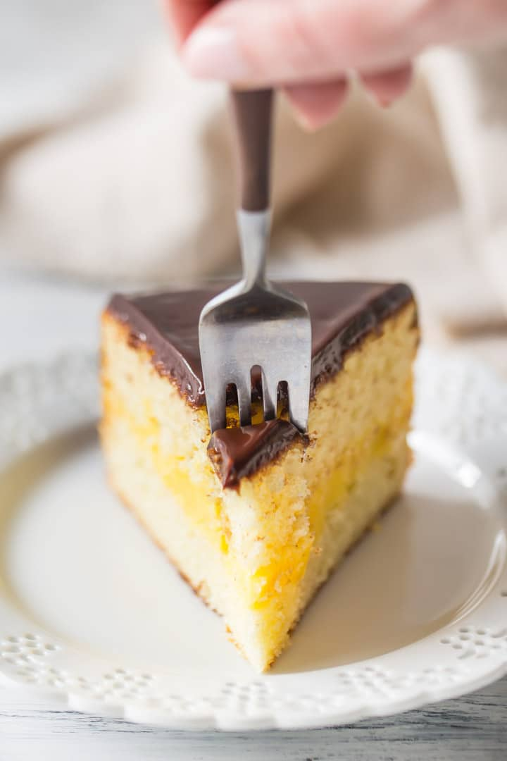 Sinking a fork into a slice of homemade Boston Cream Pie.
