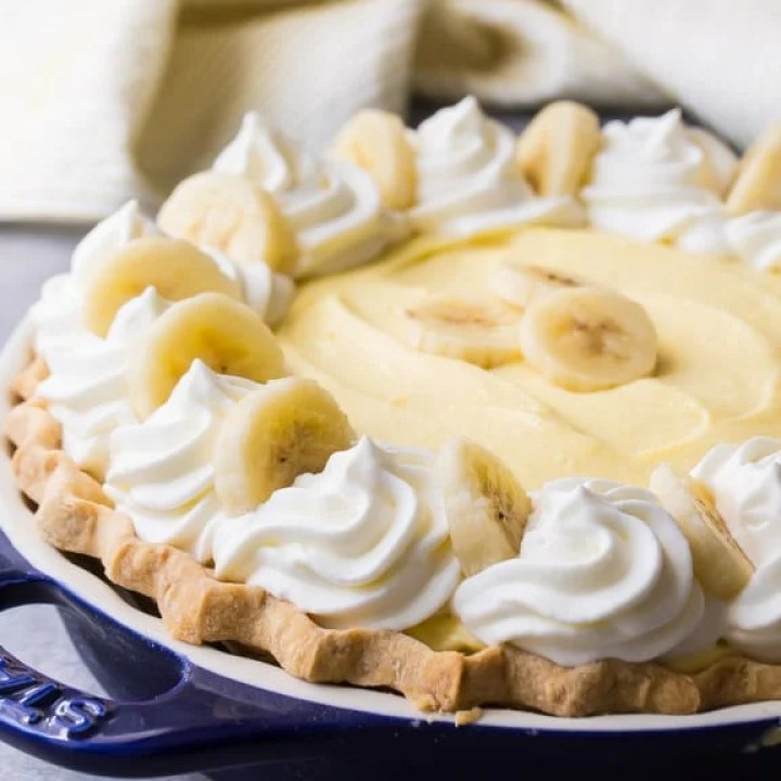 Banana Cream Pie with fluffy custard, swirls of whipped cream, and fresh bananas.