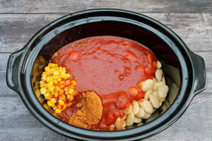 Overhead view of crockpot with chicken and tomato sauce plus beans and spices