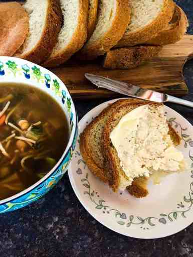 Vegan white bread shown buttered on a plate with a bowl of soup beside it