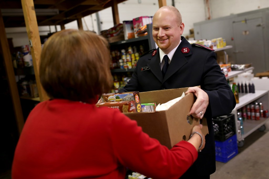 Volunteers organize boxes of food and Captain Joshua Stansbury gives the food to people in need.