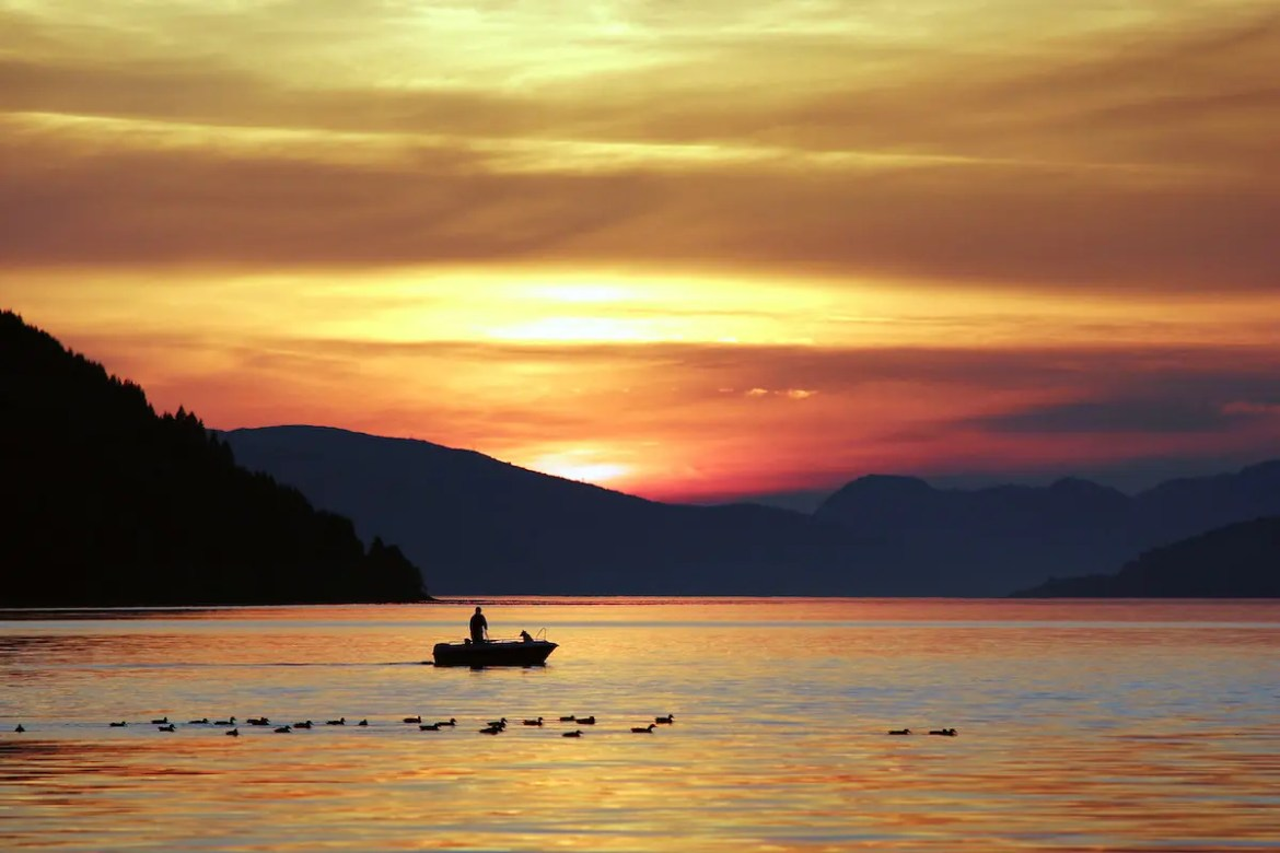 A man is seen on his boat in a lake as the sun rises above hills behind him. This picture serves as the feature image for 10 acceptance quotes because it shows how welcoming and accepting each day is vital for happiness.