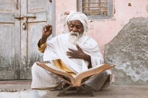 Close up of an old Indian sadhu (saint) sitting and reading sacred texts near the temple. Science and spirituality disagree on Hindu wisdom.