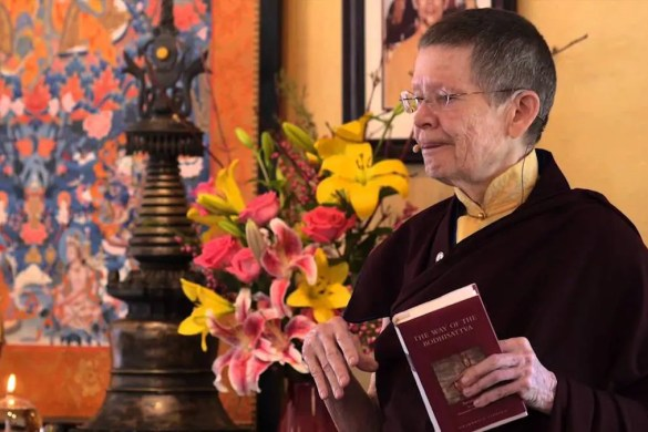 A picture of Pema Chodron giving a speech is shown. She is holding the popular Buddhist book The Way of a Boddhavista.