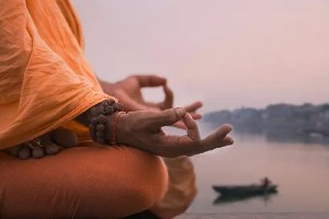 Meditation allows us to increase our mindfulness, which increases our abilities to achieve goals. A man's hands are seen in the meditation Om position