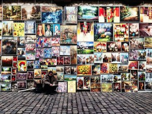 A man is shown on the street selling many of his paintings as he paints another picture. He has taken the right career path because he works in a field he is passionate about and one that allows him to use his best skills.