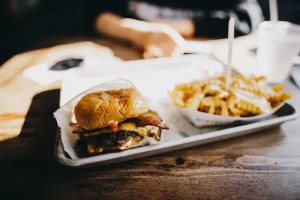 A picture is shown of a greasy burger and fries. Changing your diet with intention and attention helps to exchange food like this for more wholesome options.