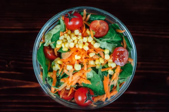 A salad bowl is shown with healthy vegetables in it. This picture represents the idea of changing your diet.