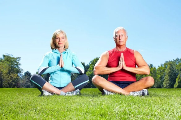 An older couple sits in meditation posture. Meditation and the aging process are directly related.