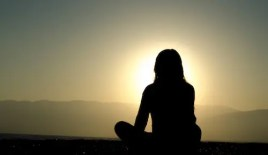 A woman's silhouette is seen as she meditates in the sunset. Meditation 101: We all have the ability to meditate without religious affiliation