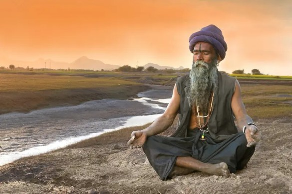 A Indian Sadhu meditates along the Ganges River. Meditation 101 explains how the roots of meditation can be traced back to the creation of Hinduism