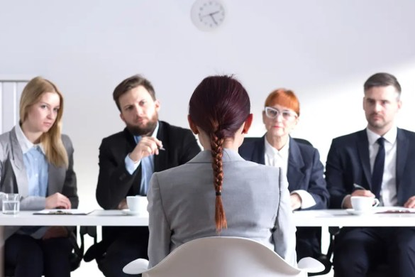 A woman is being interviewed for a job by 4 employees. You can change your emotional state by changing your body language.