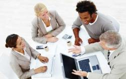 cultivating relationships at work is a major component of career advancement. A team of 4 employees sit around a table, while working on a project, with smiles on their faces.