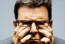How to increase willpower? Science is pointing to the fact that we need good sleep patterns. A man is shown rubbing his eyes as if he is lacking sleep.