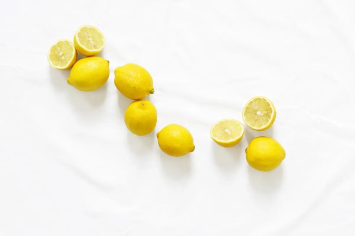 7 lemons sit on a white table cloth. The health benefits of lemons are immense.