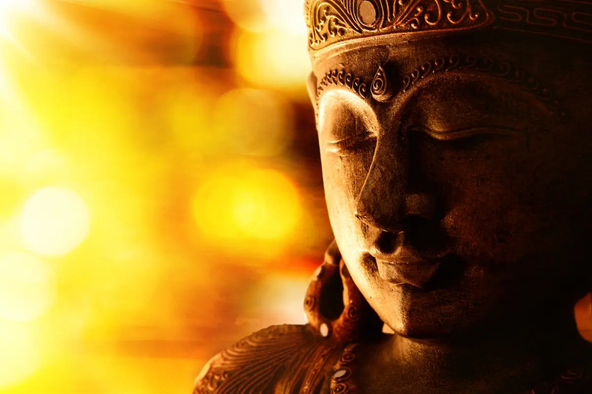 Did the Buddha Believe in a God?: a Buddha statue is shown in yellow light.