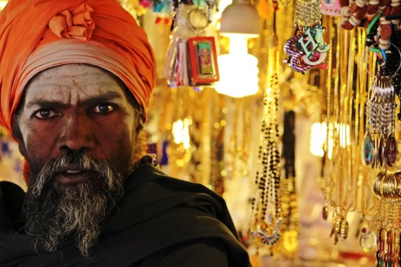 A bearded Hindu man is shown with his face painted and wearing a robbed hat with a number of Hindu shop collectables in the background. This represents the article that highlights the best documentaries about Hinduism.