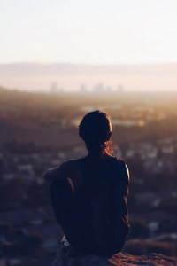 The back of a woman is shown as she sits on a rock and looks over a city. By asking yourself conscious questions, you have the ability to greatly improve your life.