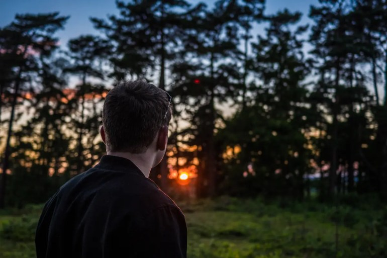 A man looks into a forest as the sun sets. He is in deep though and is asking himself conscious questions.