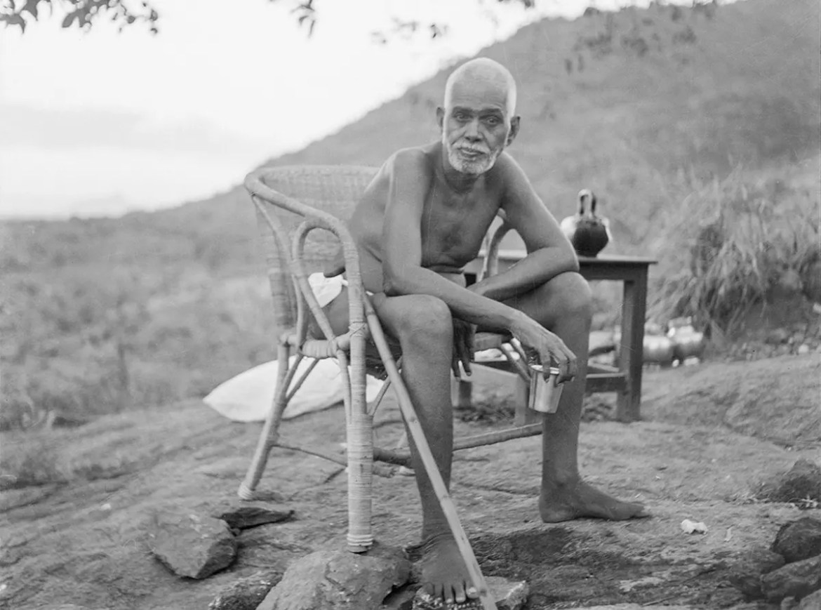 Ramana Maharshi sits in a chair bending over with the holy hill Arunachala in the background.
