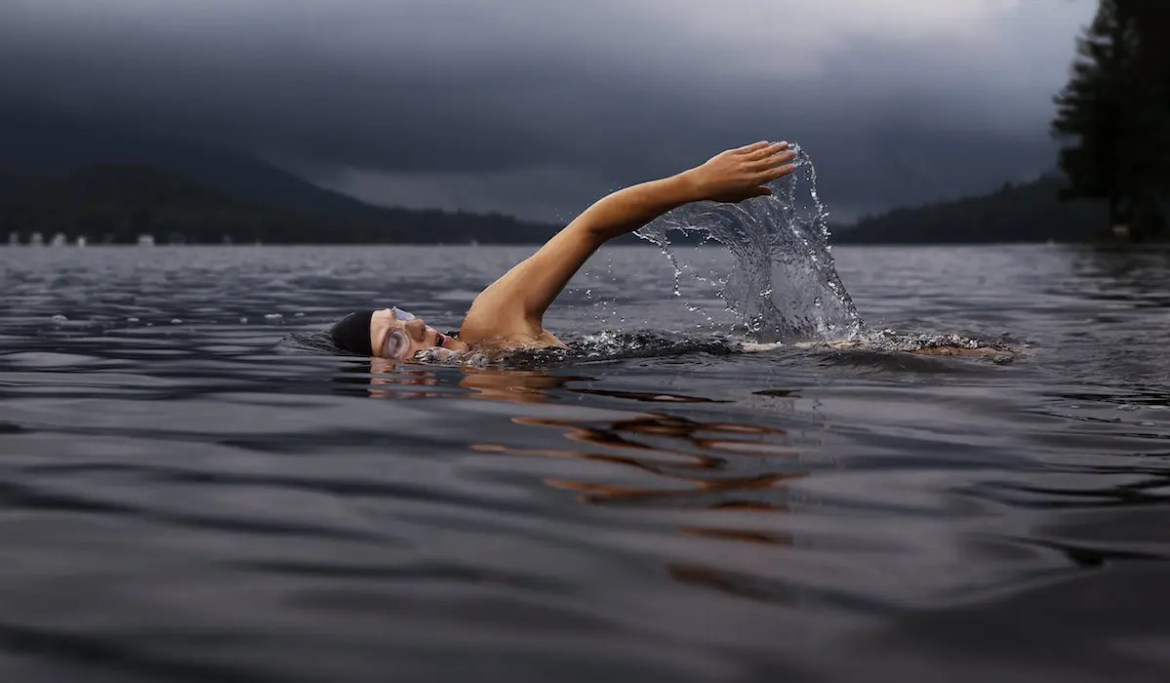A swimmer is shown in what looks like freezing cold water. This picture represents the personal quality of determination.