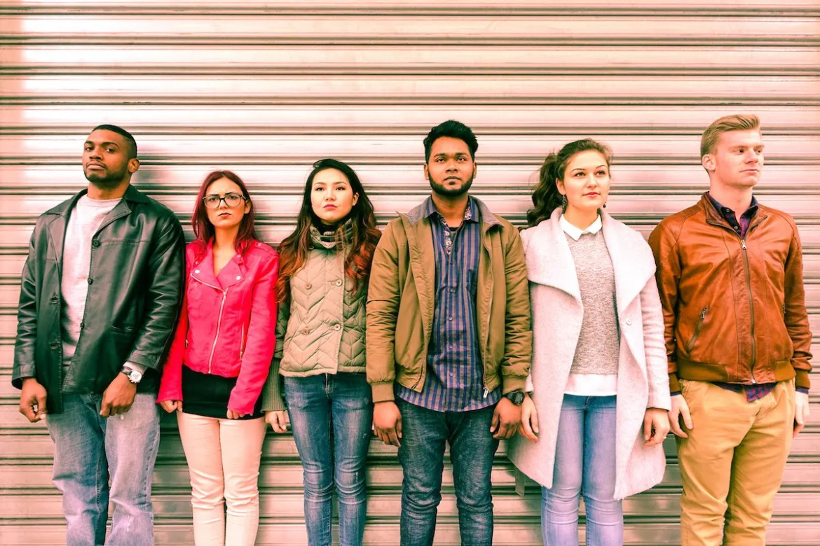 6 people of with different ethnicities and styles stand in a line infant of a metal rolling shutter. This image serves as a representation of the human tendency of judging others.
