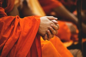 A Buddhist monk's hands are shown together in a prayer position. This picture represents the Buddha's teachings on the 3 marks of existence.