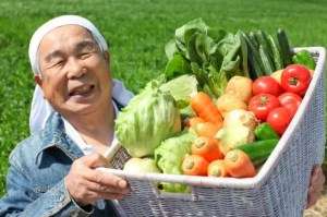 A Japanese man is shown carrying a basket full of gardened vegetables. Okinawa, Japan, is one of the blue zones hotspot that relies heavily on gardening.