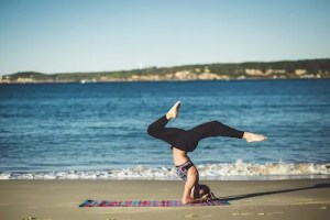 A woman is shown on the beach doing yoga. Her head is on the ground and her legs are in the air. This picture represents the body aspect of the mind, body, and soul triad.