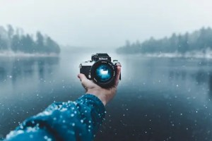 A picture of a man's hand holding a camera looking back at him is shown. The weather is snowy and the man is near a lake. This picture represents the idea that we can consciously watch ourselves and make decisions from a more conscious reference point.