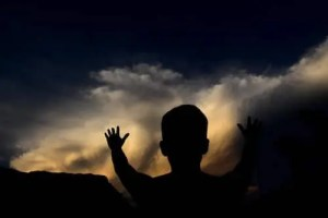 A silhouette of a man is shown with his hands in the hair. His figure is in black against a blue and yellow sky. This image represents the indescribable state of consciousness.