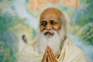 A picture is shown of the transcendental meditation founder Maharishi Mahesh Yogi with his hands in prayer position.