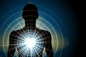 A computer generated image shows a black silhouette of a person with their heart in bright colors giving off vibrating light. This image represents the idea of metta meditation.