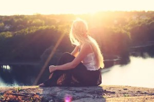 A picture of a woman is shown sitting on a rock overlooking a river. The sun is shining down on her. This picture represents the soul aspect of the mind, body, and soul triad.