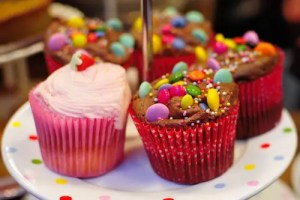 A plate is shown with 5 colorfully decorated cupcakes on it. This image represents the notion that to lose weight, individuals must control the types of foods that are in the environments they most frequent.