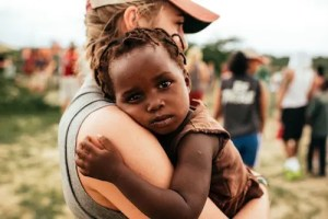 An image of a white woman is shown volunteering in Africa. She is pictured holding a poor African baby who is looking directly into the camera lens.