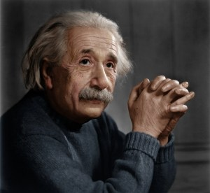 A picture is shown of Albert Einstein sitting with his hands crossed in front of his face.