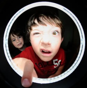 A kid is looking through a hole with a silly face. One of his eyes is half open and his sister is smiling behind him.