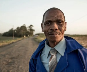 A man from Africa is shown wearing work attire on a dirt road with a smile on his face.