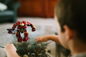 A boy is shown playing with an Ironman toy that is sitting on the table.