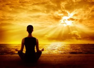A computer generated image is shown of a women meditating on a beach. The sun is brightly shining down here. This picture reminds us of the power of meditation.