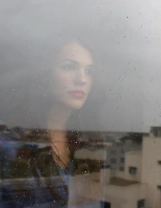 A picture of a woman is shown looking outside of a window nervously. This picture represents the idea that our basic instinctual drives act as psychological limitations.