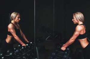 An image of a woman is shown working out with dumbbells as she looks into the mirror with determination.