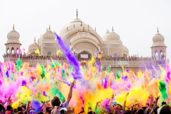 An image shows the Holi festival taking place in front of a temple of India. Large crowds of people are throwing dry colorful and washable paints into the air.