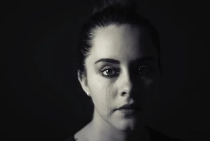 A woman is shown in a black and white portrait with a tear running down her eye and messing up her makeup.
