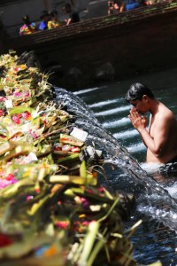A Hindu man is shown bathing in a holy river with his hands in prayer position.