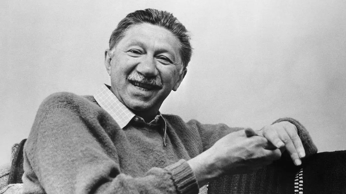 An image shows psychologist Abraham Maslow smiling while sitting on a bench. This picture serves as the featured image for Balanced Achievement's Quote 20 article which examines 20 Abraham Maslow Quotes.