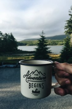 A mug is shown with the words 'The Adventure Begins' written on it and a picturesque lake and mountain sits in the background.