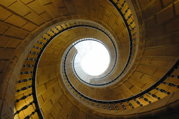 A beautiful spiral staircase is shown from the bottom floor of a building looking up at a sunny opening. This image serves as the featured image for Balanced Achievement's article looking at CBT and success.
