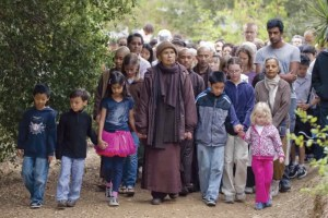Thich Nhat Hanh is shown walking on a dirt path hand and hand with children and a large crowd behind him. They are practicing walking meditation.